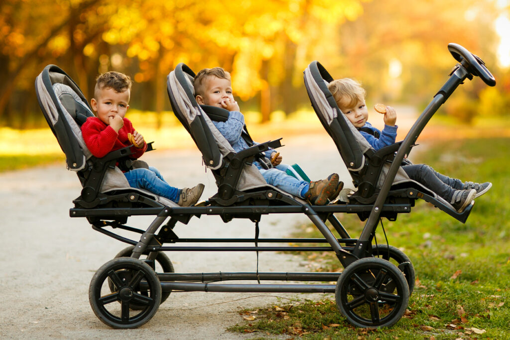 The happy triplets sit in a baby stroller