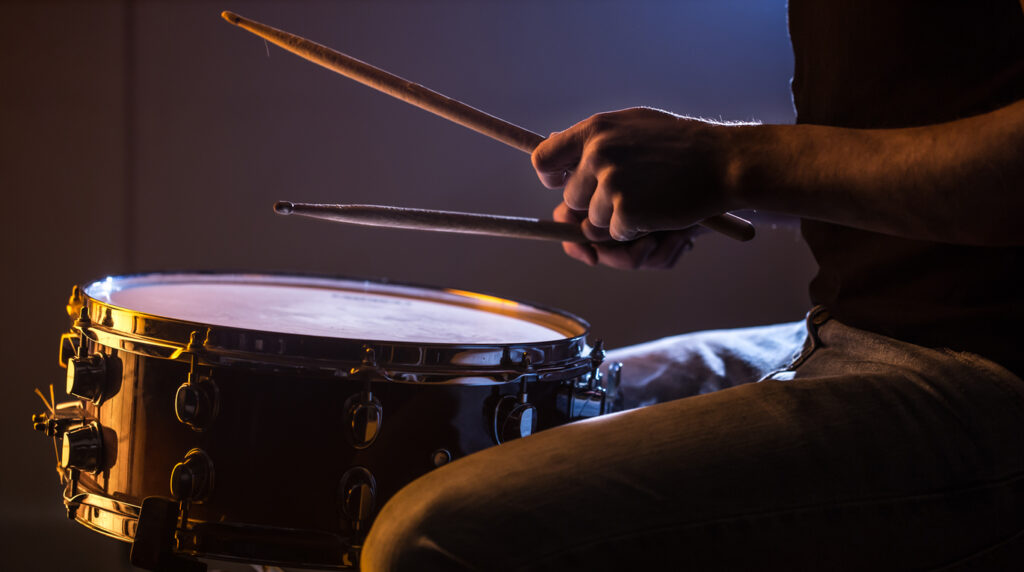 man playing the snare drum on a beautiful colored background